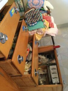 Four kitchen drawers of items include flatware, meat and candy thermometers, plastic wrap and baggies, potholders and dish towels, cookie cutters, graters, rolling pin and more