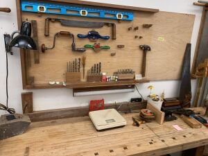Woodworking tools on and above woodworking bench includes large draw knife, hand brace and bits, Bedford draw planes, t-handled auger, handsaw, level, Brad point bits, forstner bits, calipers, saw vise, saw set and more