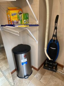 Oreck upright vacuum, Oreck handheld canister vac and accessories, 7 gallon metal step trash can, ironing board, Proctor Silex iron and cleaning supplies under kitchen sink