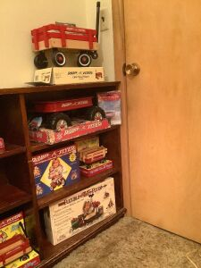 Bookcase and Radio Flyer items on right side Bookcase measures 48 x 10 x 33 Items include wagons, tricycle, sled, miniatures