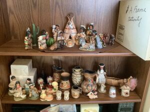 Two shelves of Native American decor-nativity scene, S&P shakers, figurines, bells, vases