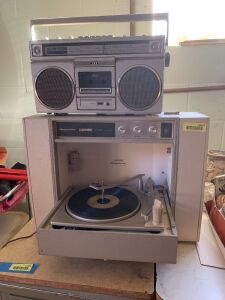 Vintage Magnavox stereophonic turntable with attached speakers and a portable AM/FM cassette boombox