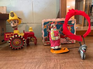 Two vintage tin windup toys one animated fire car with a fireman pops a wheelie,  the other is Cleo clown the dogs Both complete