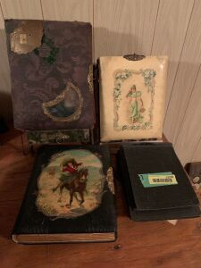 Two dresser top easel style antique photo albums, one photo album with girl on a horse on the front and four misc. empty postcard albums Photo albums all contain pictures