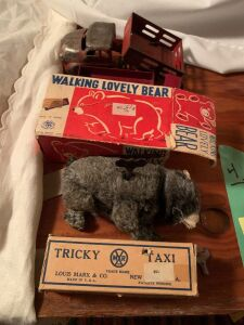 Tin wind up Tricky Taxi car by Marx, a wind up walking lovely bear with box made by Modern Toys Japan, Dinky Toys truck and a pressed tin Wyandotte toy livestock truck