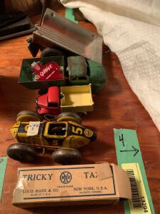 Wyandotte pressed steel dump truck, Dinky Toys dump truck, Marx No. 5 windup bobtail roadster and a Marx Tricky Taxi windup car in its box