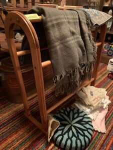 Quilt rack with wool throw, throw pillow, variety of doilies and table runners