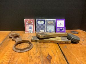 Four decks of casino playing cards, two folding Lufkin rulers, a 25' tape reel and an old wrench