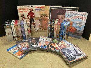 Multi media western lot! Many John Wayne DVDs, Blu-ray and VHS tapes, 50th Anniversary Remember Pearl Harbor magazine, JFK, Gene Autry Christmas and John Wayne vinyl albums