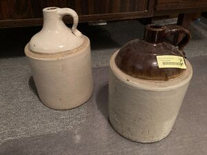 Two stoneware jugs w handles, one is a brown top  Neither are marked