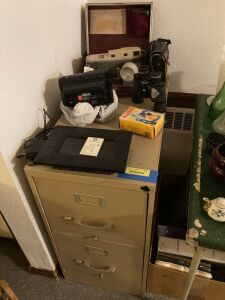 Two drawer letter file cabinet, Sony Video 8 handy cam, digital photo frame w remote, Empire binoculars, Polaroid 800 camera, box of picture frames and photo albums