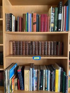 Three shelves of books including The Works of Charles Dickens
