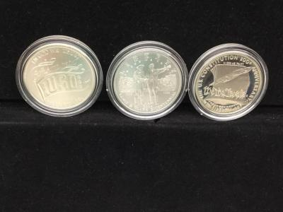 Three commemorative Dollar coins
